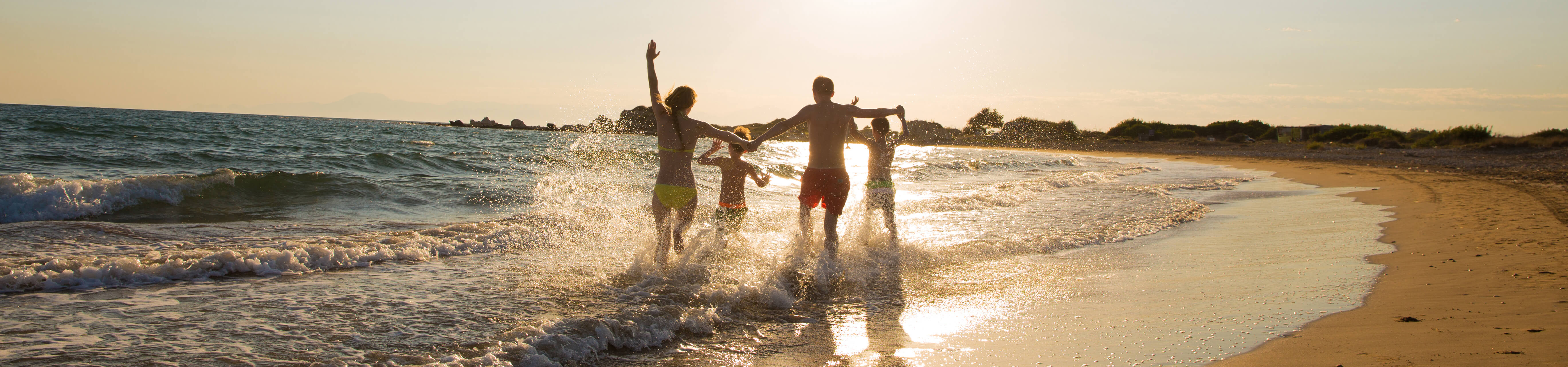 Family playing in the surf at sunset