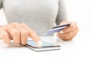 Woman with cell phone and credit card